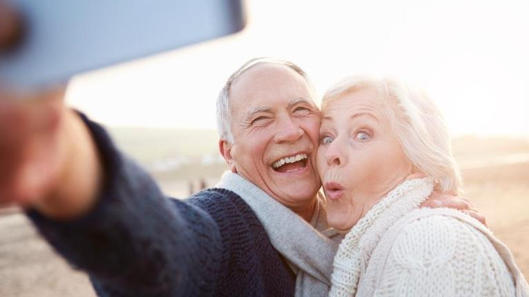 Senior couple taking selfie on the beach